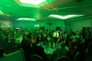 Kids Village Ball (green lit image of event room with guests)