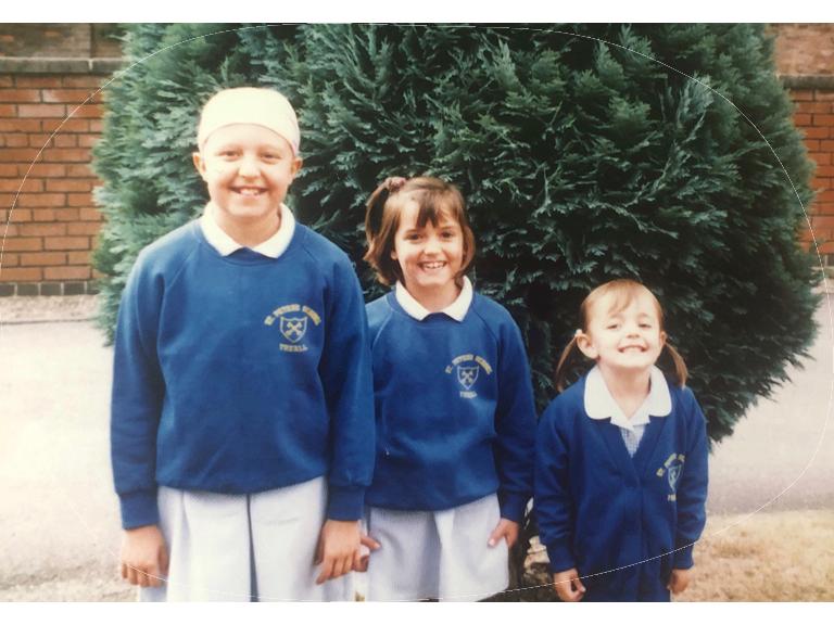 who we are Kids Village (three children in school uniforms)